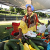 Features at Friday afternoon Lowell Farmers Market. Khadija Aliow of Manchester, NH., gathers vegetables for a customer.  Originally from Somalia, she's one of 15 farmers at Dunbarton Farm, a CSA near Manchester. (SUN/Julia Malakie)