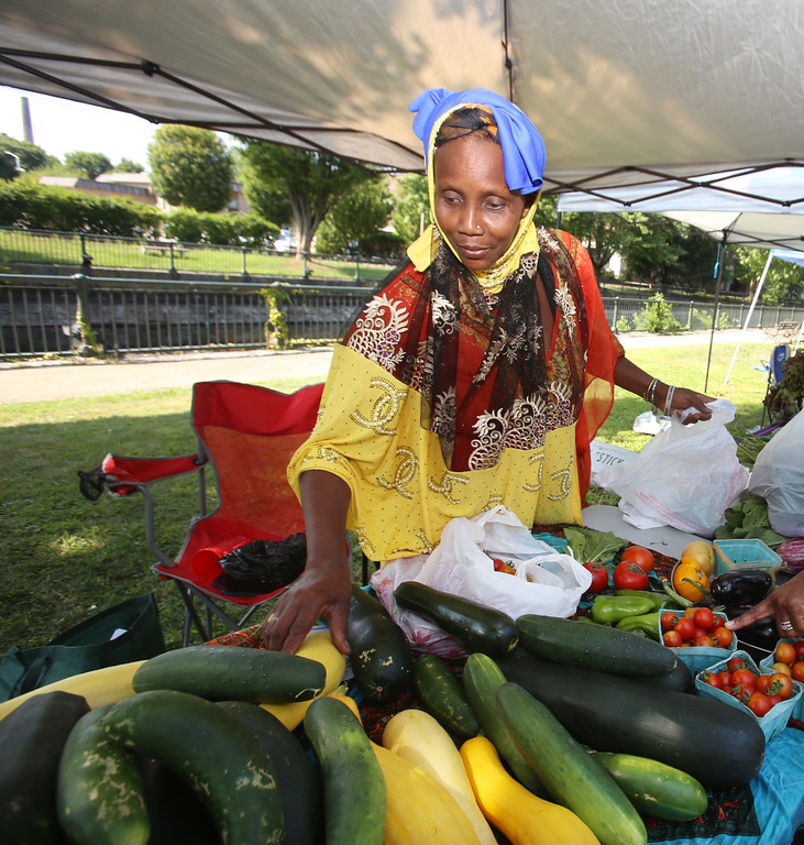 . Features at Friday afternoon Lowell Farmers Market. Khadija Aliow of Manchester, NH., gathers vegetables for a customer.  Originally from Somalia, she\'s one of 15 farmers at Dunbarton Farm, a CSA near Manchester. (SUN/Julia Malakie)