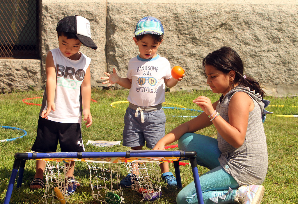 . Features at Friday afternoon Lowell Farmers Market. From left, Maddox Chak, 2, Adam Al Maliki, 2, and his sister Mina Al Maliki, 9, all of Lowell, play with a bean bag toss game. (SUN/Julia Malakie)