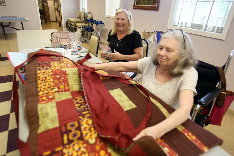 Quilting and pool players at the Lowell Senior Center, which will be a place to stay cool this weekend. Evelyn Miller, left, and Pamela Howland, both of Lowell, look at Howland's quilt in progress. (SUN/Julia Malakie)