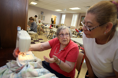 Quilting and pool players at the Lowell Senior Center, which will be a place to stay cool this weekend. Helen Gloor of Tewksbury, helps Carmen Lebron of Lowell with a simple quilt she waa making. (SUN/Julia Malakie)