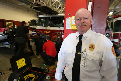 Lowell Fire Chief Jeff Winward, at Fire Department HQ. He will be retiring soon. At rear, firefighters practice rescuing a person trapped under a vehicle. (SUN/Julia Malakie)