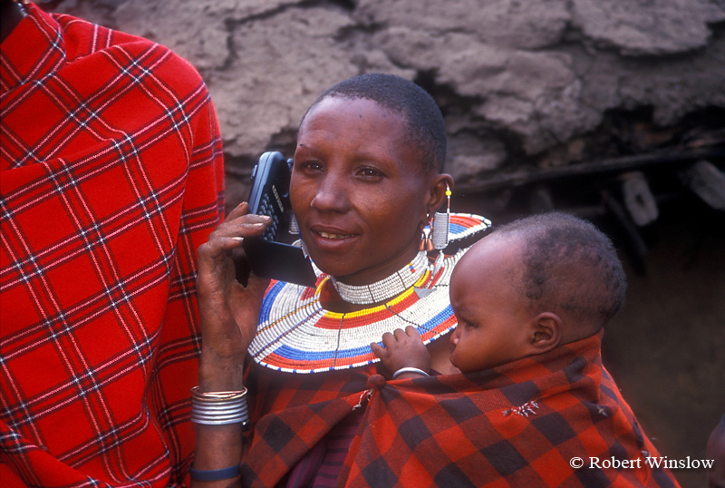 Maasai Mother Listening on Cell Phone while Carrying Baby in Village (called a Boma or Manyatta), Ngorongoro Crater Area, Tanzania, Africa