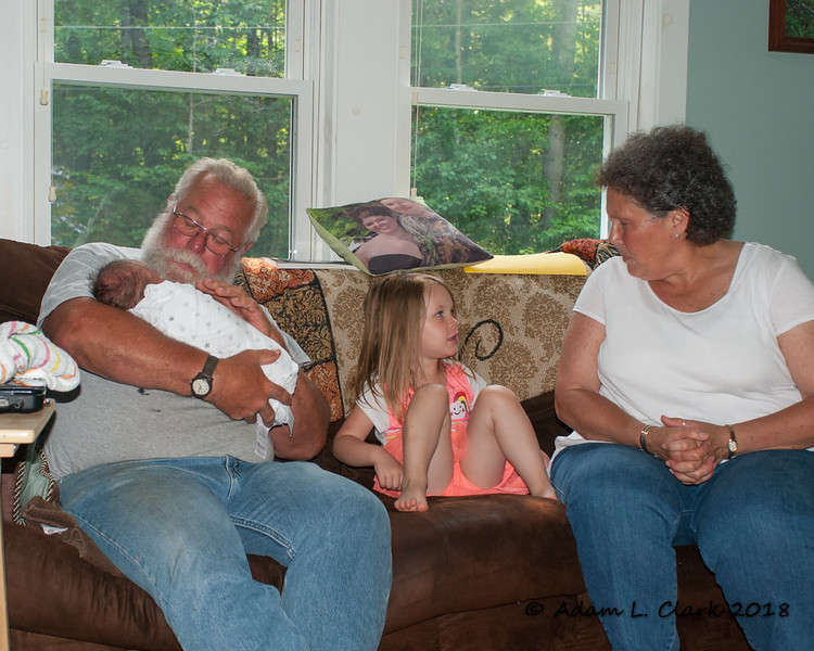 Liliana telling Grammy about the morning while Grampy holds Madison