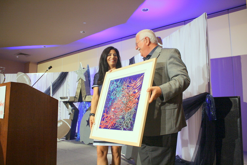 Kirk Clark presents an original painting to Alma Johnson.