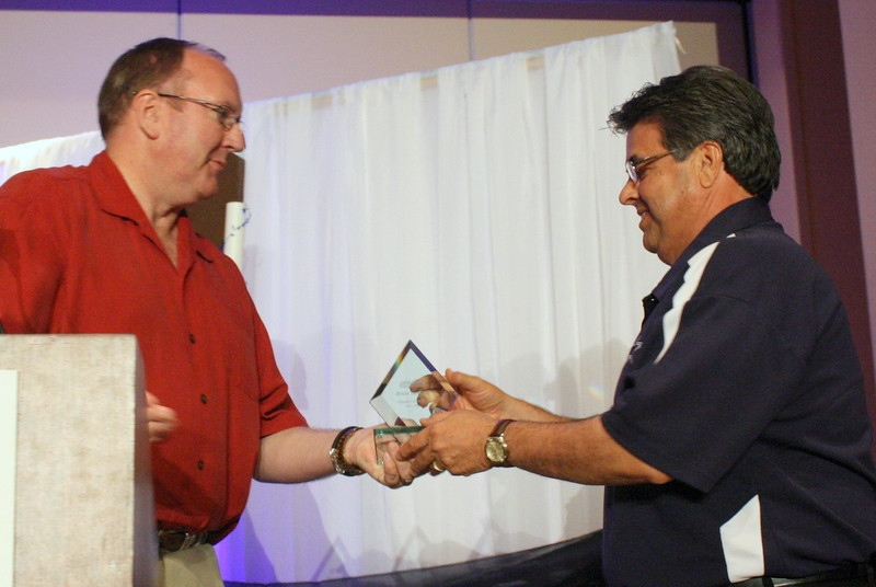 McAllen Chamber President Steve Ahlenius presents the Volunteer of the year award to Brian Godinez.