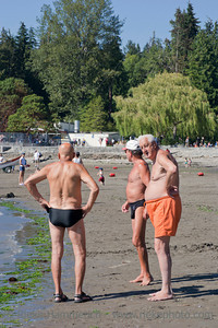 Vancouver, British Columbia, Canada – August 5, 2005: Three Senior Men standing on Second Beach in Stanley Park, Vancouver B.C., Canada. Stanley Park is an urban park of more than 400 hectare bordering downtown Vancouver and was opened in 1888.