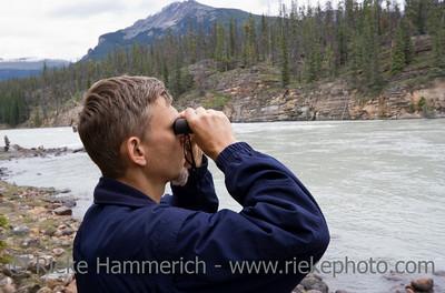 park ranger looking through binoculars - athasbasca river, jasper national park, canada
