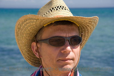 summer portrait - mid adult man with sunhat on the beach - adobe RGB