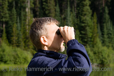 park ranger watching closely wildlife - with his field glass