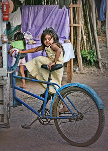young girl getting on a bicycle