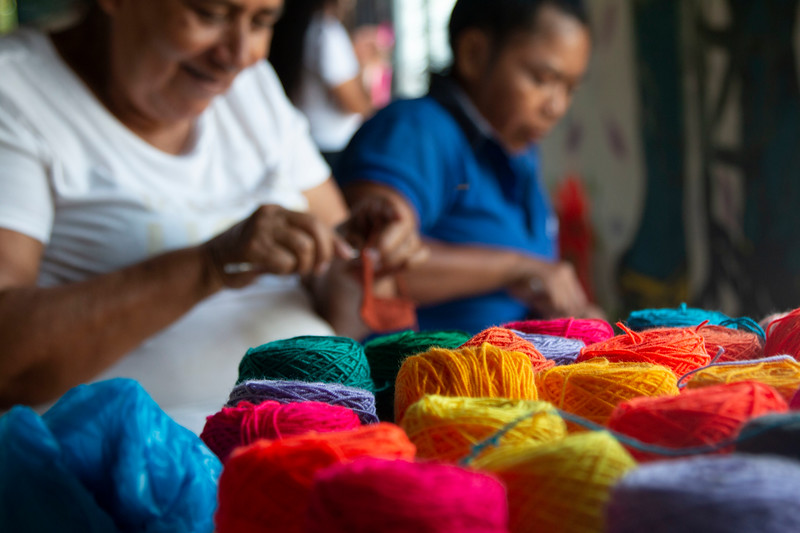 As soon as we arrive, after greetings and introductions, Cristina and Luz Dary take out their coloured threads and explain how they weave their traditional shoulder-bags or mochilas, and so without delay the women begin today's activity.