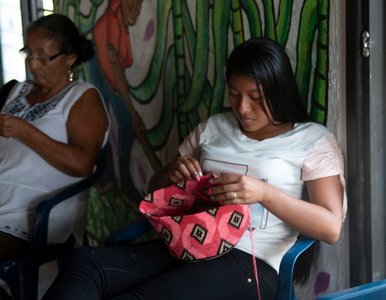 Meanwhile, Cristina continues to weave her mochila.