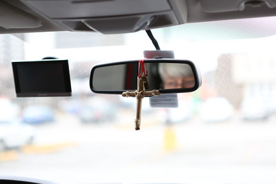A cross hangs from Michael Rover's rear-view mirror, as he travels the city making house calls.
