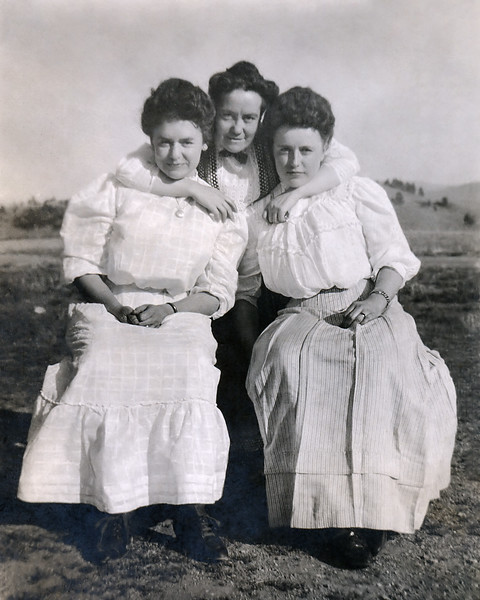 I am fairly confident that the two young women in this photograph are sisters of my great-grandmother Minnie Raver. I cannot say what sisters.  Minnie had five: Lulu, Maud, Callie, Mable, and Mary. The last two would be too young when this was taken. Both of the young women are wearing wedding rings. Callie was married in 1905 so I'm guessing this picture was taken later perhaps in 1906. The older standing women hugging the two sisters is probably Elizabeth Fulk, their mother, and one of my great-great-grandmothers. This is only a guess. There is no law of nature requiring only mothers to pose with daughters.