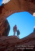 Model Released, Man and Young Girl, Father and Daughter, Holding hands and Looking out through an Arch, Arches National Park, Utah, USA