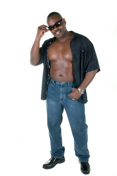 Black muscular man in shades, jeans, and unbuttoned shirt isolated on white background