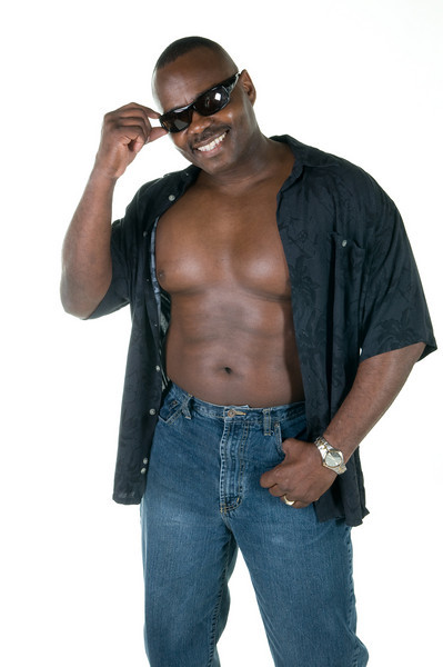 Black muscular man in shades, jeans and unbuttoned shirt isolated on white background