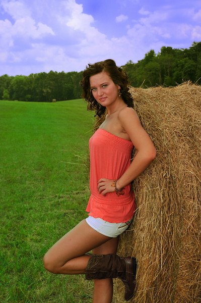 Young lady in field of baled hay