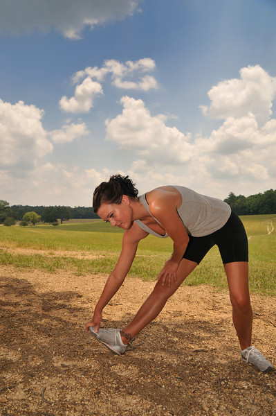 Young athletic lady stretches in preparation of running