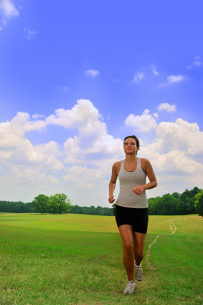 Beautiful young woman runs through the country for exercise