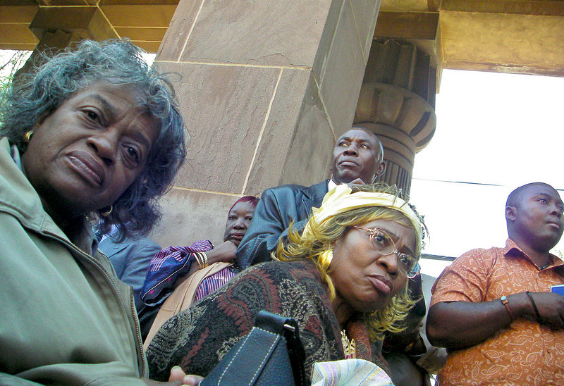 """These people were attending a memorial service under the Henry-Austin-designed Egyptian Revival entrance gate to New Haven's Grove Street Cemetery for the men from Sierra Leone who won their freedom as a result of the Amistad incident in 1839-1840.<br /> <br /> Also attending was a presidential delegation from Sierra Leone. Speakers included the Director of the Gilder Lehrman Center at Yale, the Vice-president of Sierra Leone and a beautiful Mendi singer/shaman.<br /> <br /> The Vice-president said that the government of Sierra Leone should return and commemorate the freed men of the Amistad every year. Because, he said, it was not the Portuguese who went up into the hills and captured these men. """"We did it."""" <br /> <br /> This was shot with a Pentax Optio W20 which works great for surreptitious grabs because there is no mirror slap as with (D)SLRs, you can turn all the sounds off, and unlike my D70 which finds focus with a fairly bright white light, the Pentax uses a barely perceptible red light (which I think the lady on the left spotted)."""