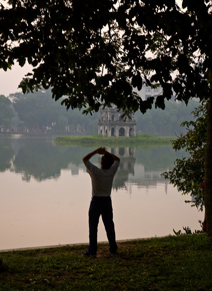 Early morning Tai Chi, Hoan Kiem Lake, Hanoi, Vietnam; Turtle Pagoda in the background