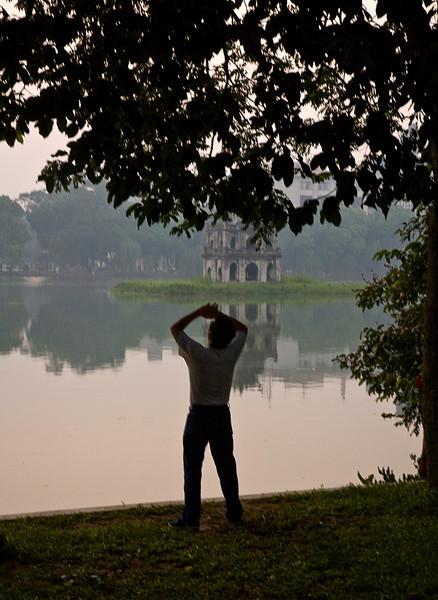 Early morning Tai Chi, Hoan Kiem Lake, Hanoi, Vietnam; Turtle Pagoda in the background