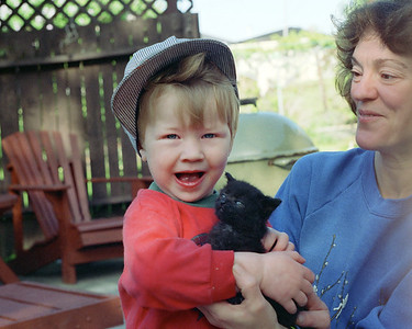 Jacob, holding a little black kitten that Donna, the lady on the side of the frame, brought over. That little black kitten grew into an accomplished killer. I once saw this cat jump from the top of our patio fence and catch a bird in mid-air. As you might expect, such a stone-cold killer was not the most cuddly of cats. Donna eventually took the little beast back and put it on vermin patrol in her garden, where I am sure it excelled.
