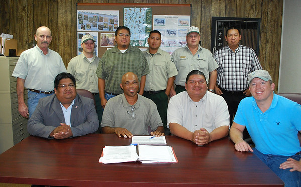 The Alabama-Coushatta Tribe of Texas recently enrolled upwards of 400 acres of suitable longleaf pine production land into the Wildlife Habitat Incentives Program (WHIP) administered by the USDA-Natural Resources Conservation Service. Sitting from left to right (front row) at the contract signing are Alabama-Coushatta Tribal Council Chairman Carlos Bullock, Ronald Harris, NRCS district conservationist, Kyle Williams, Tribal Council vice chairman and Jim Rogers, NRCS wildlife biologist. Sitting from left to right (back row) are John Davidson, NRCS-Resource Conservation &Development coordinator, Steve Cooke, TFS district forester, Tribal member Kerwin Williams, Maynard Williams, TFS, Rusty Smith, TFS and Tribal Forestry Director Don Sylestine.<br /> NRCS photo by Beverly Moseley.