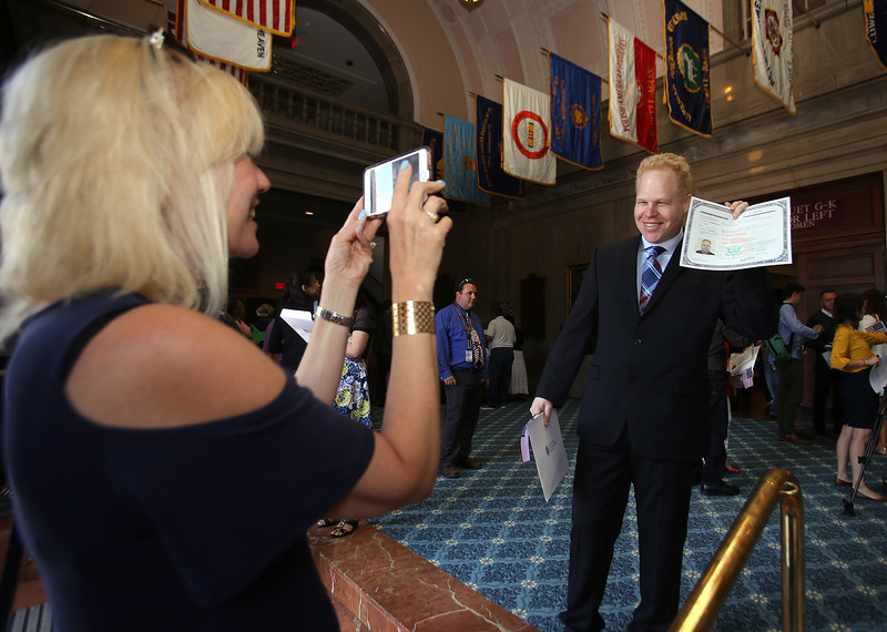 Newly sworn in U.S. citizens and friends and family leave Lowell Memorial Auditorium after naturalization ceremony. Arlene Dumont takes a picture of her husband Paulo Dumont, who'd just become a citizen. They live in Framingham, and Paulo is originally from Brazil. (SUN/Julia Malakie)