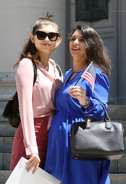 Newly sworn in U.S. citizens and friends and family leave Lowell Memorial Auditorium after naturalization ceremony. Millena Szytko, 16, left, and her mother Jucelia Szytko, who'd just become a citizen. They live in Watertown, and Jucelia is expecting another daughter in October. (SUN/Julia Malakie)
