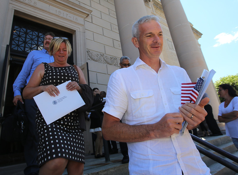 Newly sworn in U.S. citizens and friends and family leave Lowell Memorial Auditorium after naturalization ceremony. New citizens Paula and husband Richard Pearce of Swampscott, originally from Wales. (SUN/Julia Malakie)