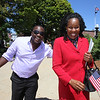 Newly sworn in U.S. citizens and friends and family leave Lowell Memorial Auditorium after naturalization ceremony. New citizen Jacintha Guillet of Waltham, right, originally from Uganda, with her roommate Halson Muwanga, who will become a citizen next year. (SUN/Julia Malakie)