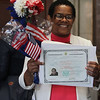 Newly sworn in U.S. citizens and friends and family leave Lowell Memorial Auditorium after naturalization ceremony. New citizen Magda Cardoso of Brockton, originally from Cape Verde. (SUN/Julia Malakie)