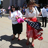 Newly sworn in U.S. citizens and friends and family leave Lowell Memorial Auditorium after naturalization ceremony. Carolina Alcantara of Hyannis, right, who'd just become a citizen, and her mother Guiomar Alcantara of Curitiba, Brazil, who is visiting for the occasion, do a dance for the video app Boomerang. (SUN/Julia Malakie)