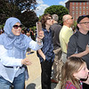 Newly sworn in U.S. citizens and friends and family leave Lowell Memorial Auditorium after naturalization ceremony. Badra Belouazani of Boston, originally from Algeria, who'd just become a citizen herself, takes picture of friends. (SUN/Julia Malakie)