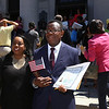 Newly sworn in U.S. citizens and friends and family leave Lowell Memorial Auditorium after naturalization ceremony. Marie Victor, left, who was already a citizen, and her husband and new citizen Sander Juste, of Salem, MA. They're originally from Haiti.(SUN/Julia Malakie)