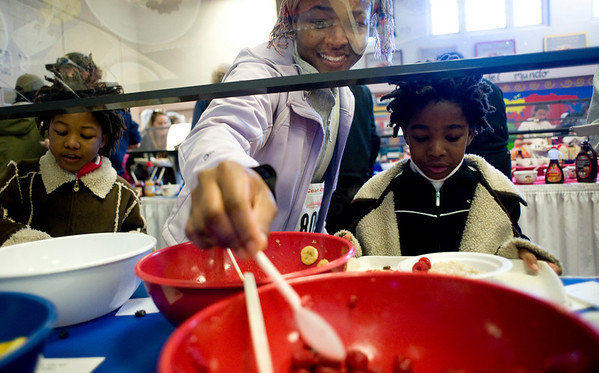 Mirands Wade, of Boulder, helps with the toppings for her children Norvinya, 6, (left) and Fafa, 7, during the annual Oatmeal Festival at Pioneer Elementary school in Lafayette, Saturday, Jan. 9, 2009. <br /> KASIA BROUSSALIAN