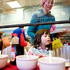 Delaney Watson, 3, chooses between toppings while her mother, Heather Watson, of Boulder, helps and Lisa Wood (left) of Westminster, waits behind during the annual Oatmeal Festival at Pioneer Elementary school in Lafayette, Saturday, Jan. 9, 2009. <br /> KASIA BROUSSALIAN