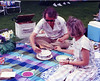 Ruth and I setting fire to the joint birthday cake for Gayle and Howard during a picnic at Tanglewood