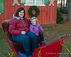 Liliana and Melissa sitting in an old sleigh after we loaded our tree into the truck