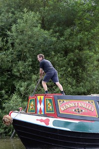 Bargee using a bargepole on Kennet Valley on the Kennet and Avon Canal