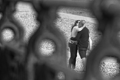 Couple Embracing on Brighton Beach snapped through sea front railings whilst seated