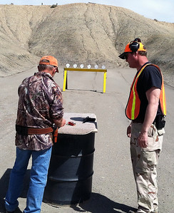 A range master coaches a shooter during the Green River 3-gun Shoot Competition. Photo taken 04-12-14 by Brent Stettler, Utah Division of Wildlife Resources.
