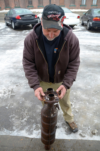 Paul Orlando, owner of Orlando Auto Sales on River St. in Fitchburg, shows a catalytic converter on Friday, that was cut out from a vehicle at his shop and was left behind. There have been a series of catalytic converter thefts in the city recently.<br /> SENTINEL & ENTERPRISE / BRETT CRAWFORD