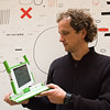 "Swiss designer Yves Béhar looking at his baby, the ""XO Laptop"" (a.k.a. $100 laptop)."