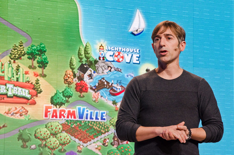 Zynga founder Mark Pincus in front of a multimedia screen showing the titles of some of his company's hit games.