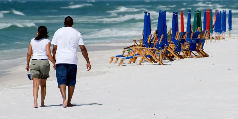 Two people walk down the beach in Destin, Florida.