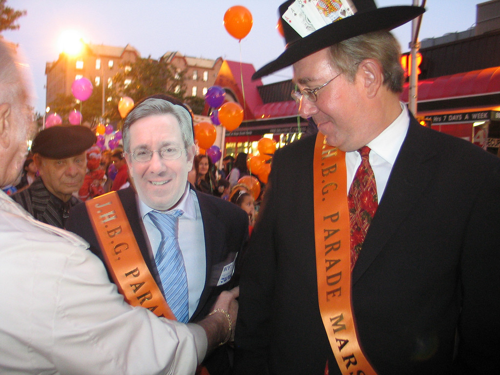 An admirer wears a John Sabini mask as the senator looks on at the 2005 Jackson Heights Halloween Parade.  Photo © Shams Tarek (shams.m.tarek@gmail.com)